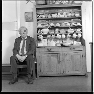 "From the McMullen Museum's ""Literary Lives"" exhibit, photograph byBobbie Hanvey (1945–), Seamus Heaney in the Kitchen of His Dublin Home, Taken At the Kitchen Table and At the Dresser, ca. 1993. Ten black-and-white negatives (60 mm) Bobbie Hanvey Photographic Archives, John J. Burns Library, Boston College, series 10, Seamus Heaney, subseries A, original accession 2001, 1979–1999, item 7 (photograph courtesy of Bobbie Hanvey Photographic Archives, John J. Burns Library, Boston College)"