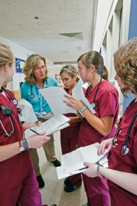 "Photo from ""Rookies"" by Amy Sutherland, Boston College Magazine, Winter 2010, Nursing students with Professor Stacey Barone (in blue) on the medical oncology floor of Beth Israel Deaconess Medical Center. Photograph by Gary Wayne Gilbert."