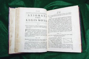 Pictured here are pages 12 and 13 of Book I of the Principia, 1723 edition, where Newton's three laws of motion appear.  Newton's Laws mark the transition from Natural Philosophy to modern science and form the foundation of physics.  Newton's Laws of Motion, faithfully translated from Newton's Latin, are as follows: Law I   All bodies persist in their state of rest or move uniformly in (fixed) direction, except to the extent that an impressed force is known to change their state. Law II.  The change of motion is proportional to the force impressed and occurs in the straight line along which that force presses.  Law III.  Reaction is always opposite and equal to the action:  that is mutual actions of (any) two bodies are always equal and oriented in opposite directions.  Translation by Professor Andrzej Herczynski.  Photograph by Lee Pellegrini.
