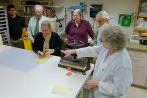 "Hebard shows a Jesuit binding to some of the visitors who attended her presentation, ""Bookbindings in the Era of Father Matteo Ricci, S.J."" Photograph by Shelley Barber, Library/Archives Assistant, Burns Library."