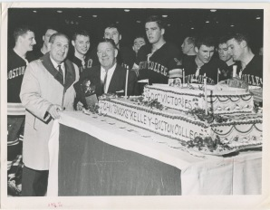"John ""Snooks"" Kelley poses next to a giant celebration cake for his 400th hockey win, Box 3, Boston College Athletic Photographs, BC.1986.019, John J. Burns Library, Boston College."