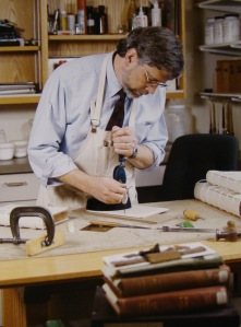 """Mark Esser drills a binder board while preparing the boards for lacing-in, from <a href = """"https://archive.org/stream/bostoncollegemagsp2000bos#page/n21/mode/2up""""> Construction Worker</a> by Anna Marie Murphy, <i>Boston College Magazine</i>, Spring 2000, p. 20-21."""