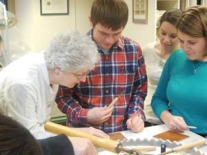 Students working in the Burns Conservation Lab -  from left to right: Barbara Adams Hebard, Christopher Petroff '15 blind tooling, Kelli Farrington graduate student, Marie Pellissier '15.