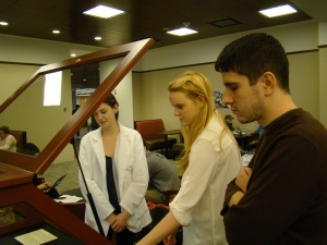 Conservation assistants Anna Whitham '15 (on left) and James Heffernan '15 help Emma Dwyer '16 install one of the class's exhibits in the O'Neill Reading Room. Photograph by Burns Conservator Barbara Adams Hebard.