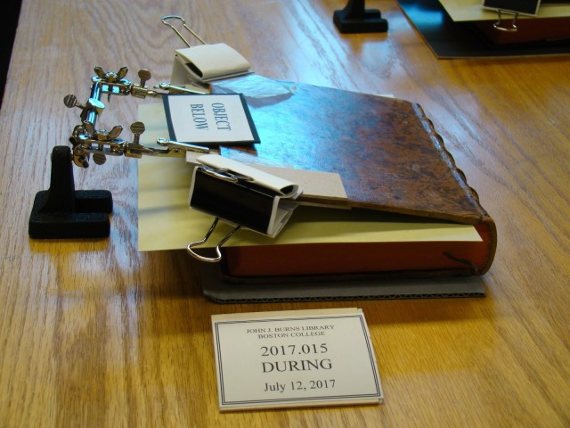 Photograph of a book being repaired with boards, binder clips, and helping hands