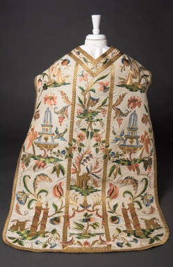 White chasuble with elaborate embroidery of flowers, candles and fountains