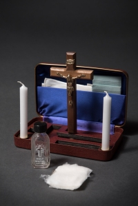 Small wooden box with crucifix, two candles, oil, and cloths