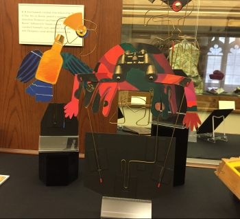 Three paper and wire puppets mounted on black cardboard to stand upright