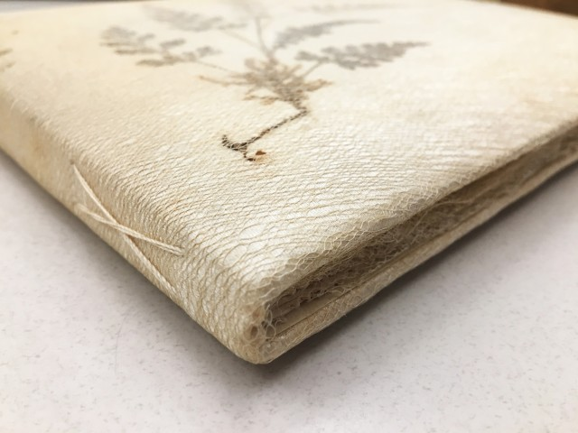 Close up of scrapbook, showing linen overlay and hand-stitched binding.