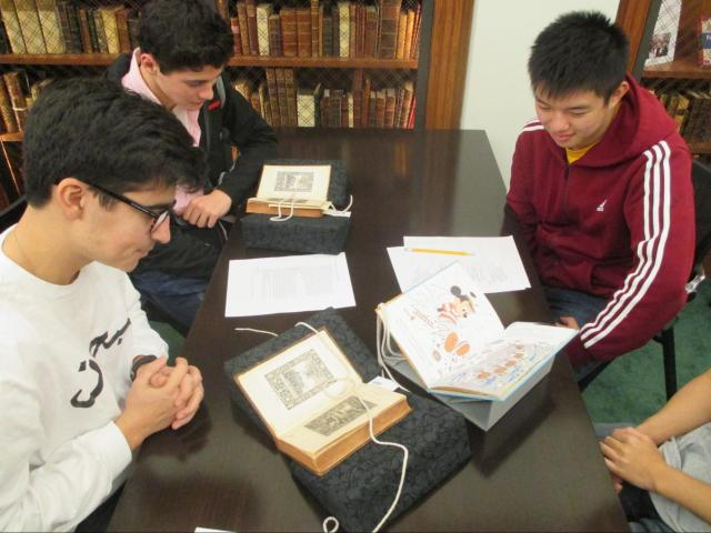 Three students examining books