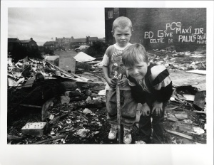 photograph of two boys in a debris-filled lot