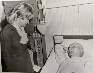 Photo of Margaret Heckler visiting veteran Oscar Mageau in the Respiratory Care Unit at the Brockton Veterans' Administration Hospital, February, 1977.