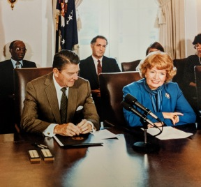 Photograph of Margaret Heckler and President Reagan at the bill signing for the Child Support Enforcement Amendments of 1984, August 16, 1984.
