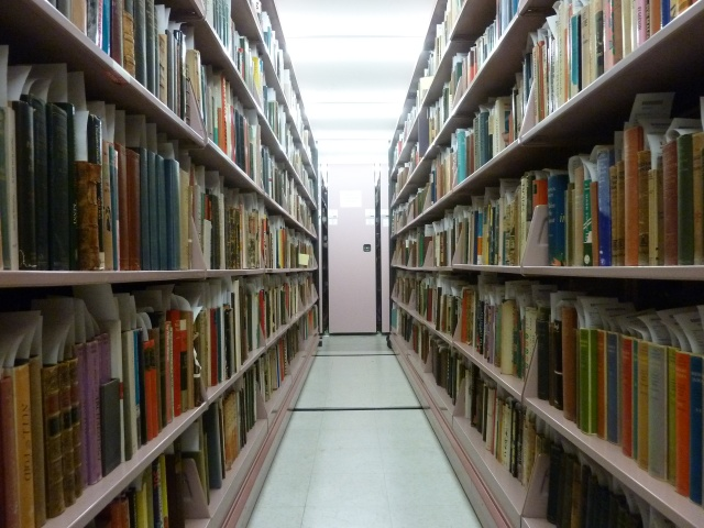 Two long rows of shelves, filled with books, from the stacks of Burns Library