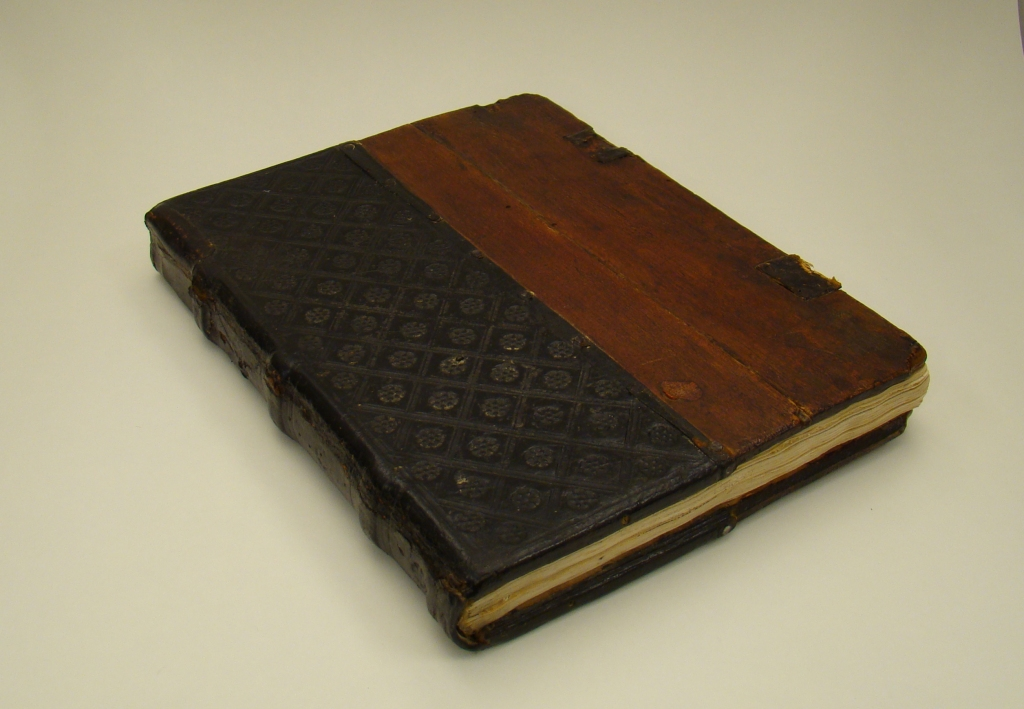 Front cover of a book, one half covered with black leather, one half has exposed wood