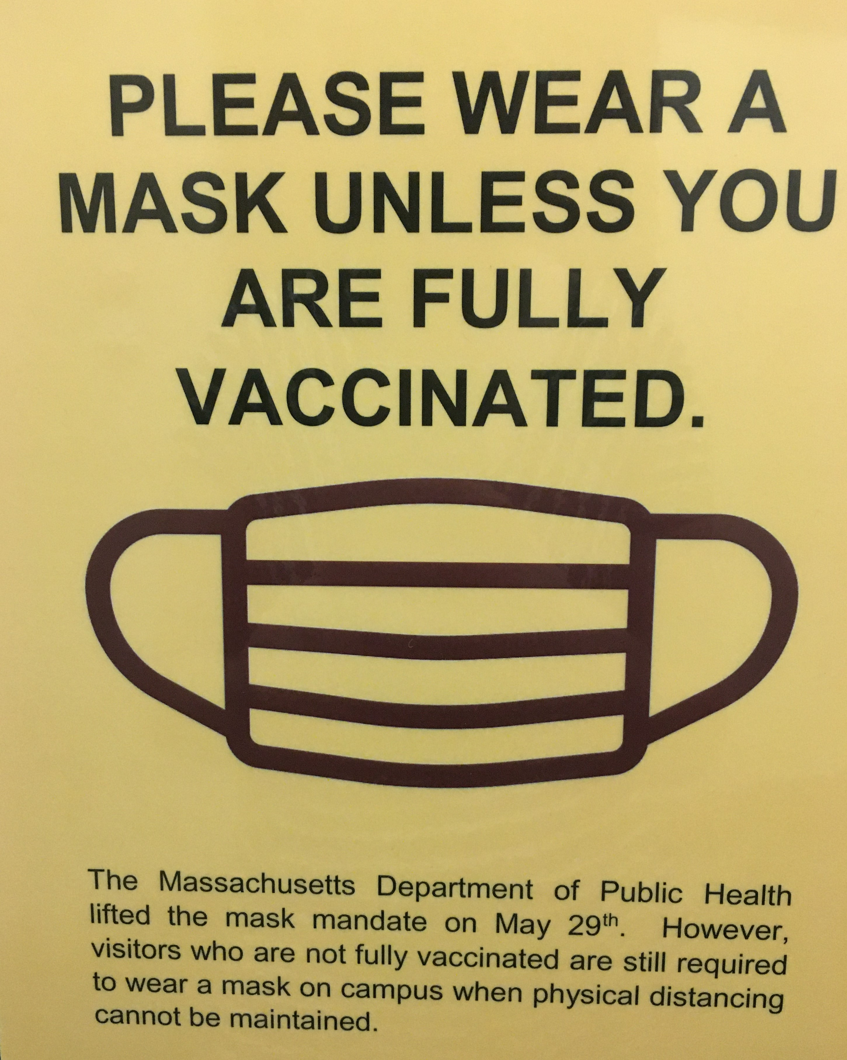 """Sign reading """"Please Wear A Mask Unless You are Fully Vaccinated."""" Smaller text underneath reads """"The Massachusetts Department of Public Health lifted the mask mandate on May 29th. However, visitors who are not fully vaccinated are still required to wear a mask on campus when physical distancing cannot be maintained."""""""
